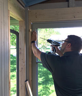 Use drill to secure window with screws